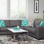 Симпатичный серый диван с интересными бирюзовыми подушками