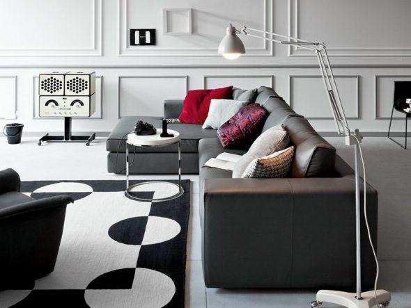 Темно-серый угловой диван с красными подушками