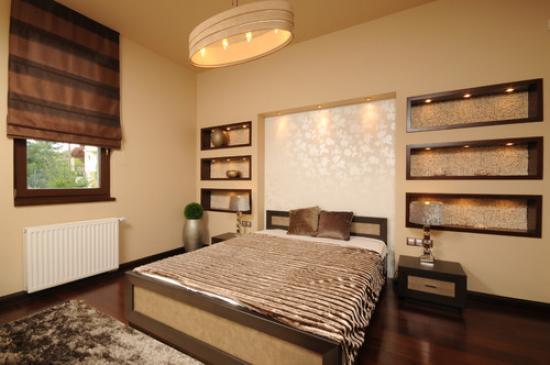 Красивые ниши из гипсокартона с декоративной подсветкой на стене у изголовья кровати в спальне