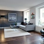 Сочетание белых и серых обоев на стенах комнаты и деревянный пол