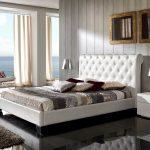 Кровать и кресла в спальне изготовлены из белой кожи