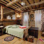 Кровать из массива дерева в интерьере дачного дома