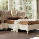 Аристократичная спальня с кроватью с высоким изголовьем необычной формы