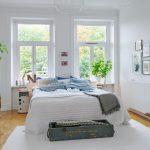 Белая спальня с кроватью изголовьем к двум окнам