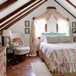 Кровать с балдахином изголовьем к окну в мансарде