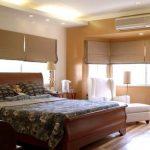 Кровать с изогнутой спинкой в угловой комнате с большими окнами