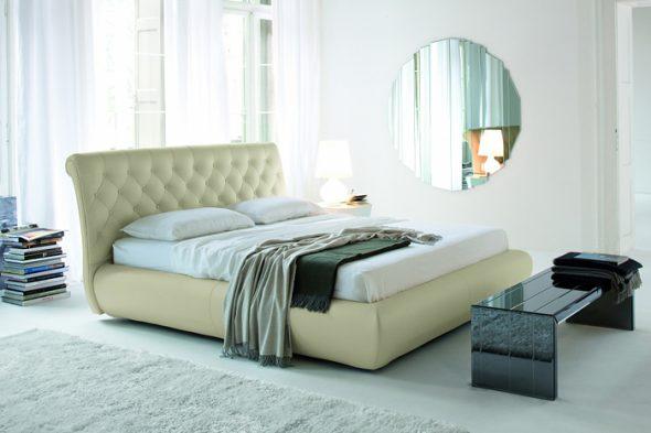 Кровать с высоким мягким изголовьем, расположенная на расстоянии от окна