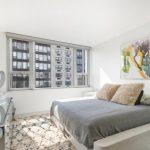 Кровать в стиле минимализм в комнате с окнами на две стены