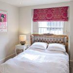 Маленькая спальня для девочки с изголовьем кровати у окна