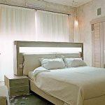 Необычная светлая кровать, повернутая изголовьем к окну