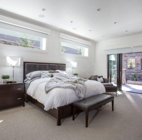 Просторная большая и светлая спальня со стеклянными дверями и узкими окнами