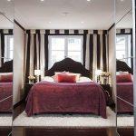 Шикарная кровать у окна в комнате с зеркальными шкафами
