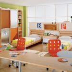 Спальня для двух подростков с кроватями у окна с большим письменным столом для двоих