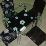 Круглый стеклянный стол и черные стулья
