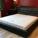 Черная кожаная кровать с мягкой спинкой