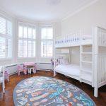 Детская комната с белой деревянной кроватью в два уровня