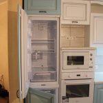 Холодильник, встроенный в шкаф и выполненный в том же цвете и материале, как и весь кухонный гарнитур