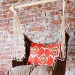 Подвесное тканевое кресло возле кирпичной стены