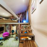 Длинная стильная комната с кроватью вверху