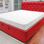 Красная кожаная кровать с обивкой изголовья капитоне