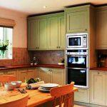 Высокие кухонные шкафы в зеленом цвете