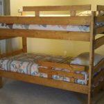 Простая деревянная кровать с защитными быльцами в два яруса