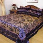 Красивое фиолетовое покрывало и подушки с необычными узорами