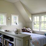 Тумба-стеллаж делает изголовье кровати более защищенным в спальне на мансардном этаже