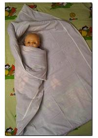 Левым концом одеяла плотно оборачиваем малыша
