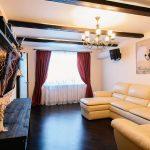 Длинные бордовые шторы в зал с бежевым диваном