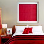 Красная штора с пружинным механизмом в интерьере спальни