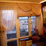 Комбинация римской шторы с портьерами на балконном окне
