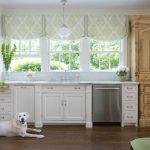 Белая собака на ламинированном полу кухни