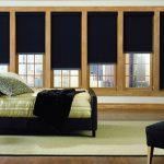 Темно-коричневые шторы рулонного типа на окне спальни