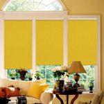 Желтые шторы рулонного типа на арочном окне