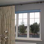 Бежевая занавеска на окне спальной комнаты