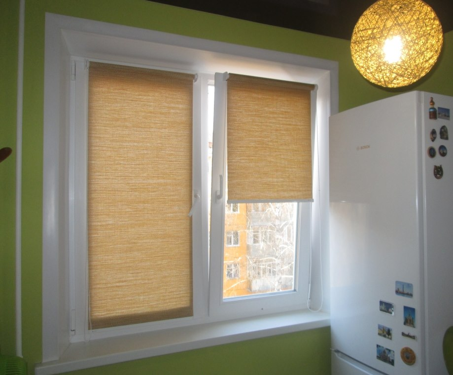 Приоткрытая створка пластикового окна с рулонной шторой