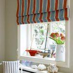 Полосатые рулонные шторы закрывают подоконник и окно целиком