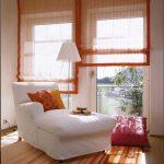 Полупрозрачные оранжевые римские шторы, закрепленные на стену