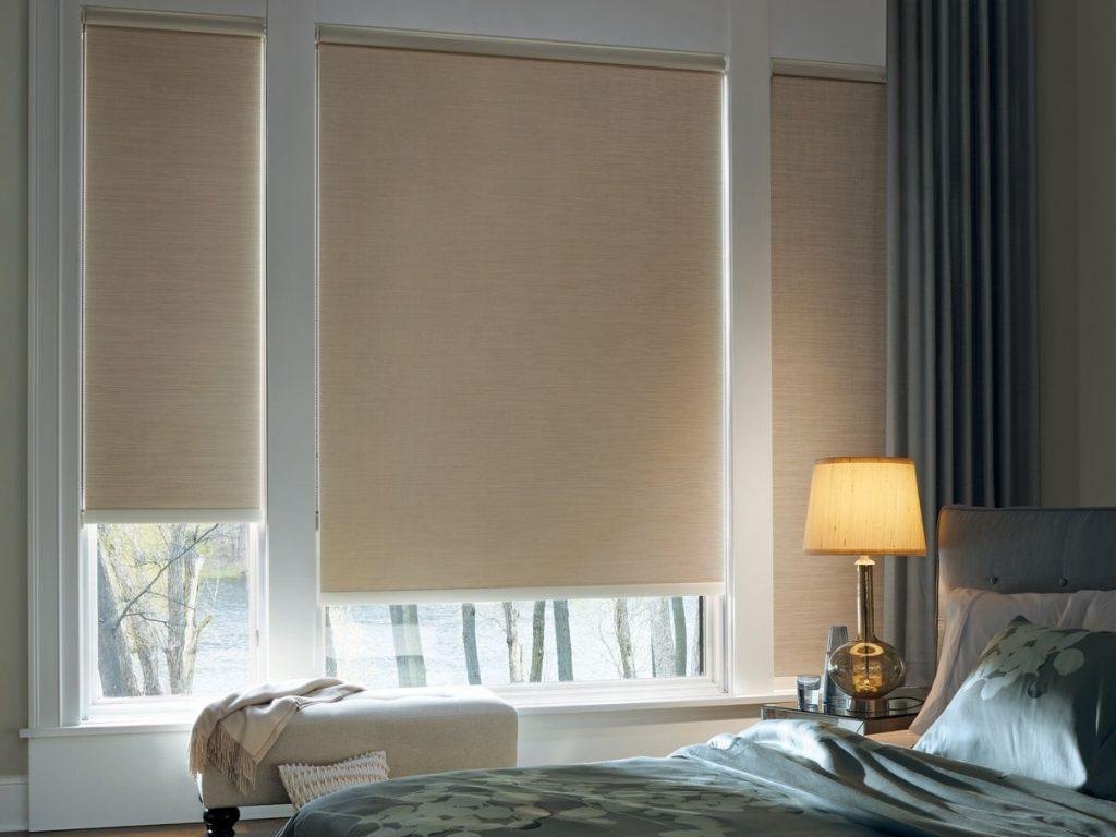 Светло-коричневая штора блэкаут рулонного типа на окне спальной комнаты