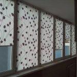 Синтетические шторы рулонного типа на застекленном балконе