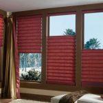 Рулонные бордовые шторы и золотисто-бордовые занавески для гостиной