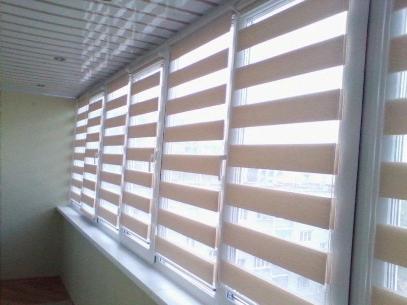 Окна лоджии с рулонными шторами день-ночь бежевого оттенка