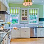 Светлая просторная кухня имеет светло-зеленую акцентную стену и зеленые шторы с белыми полосами