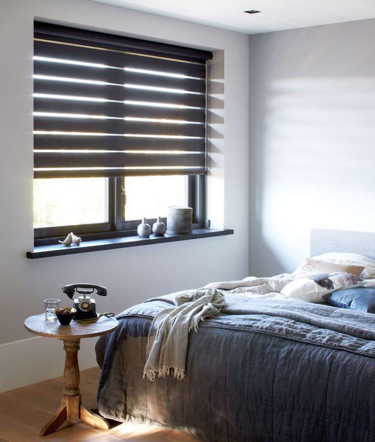 Рулонные шторы внутри оконного проема в спальной комнате