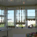 Комбинированные прозрачные и с рисунком римские шторы на эркерном окне