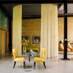Отделение зоны отдыха от гостиной с помощью штор, закрепленных на потолочных карнизах
