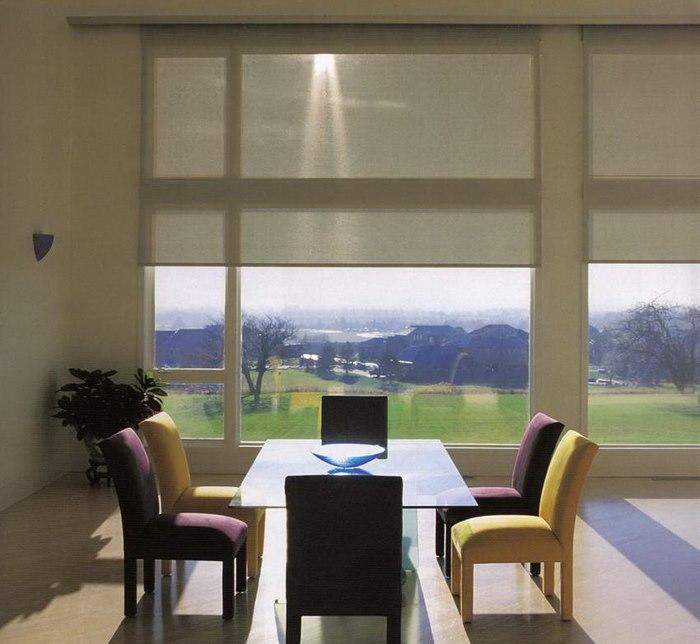 Шторы из полупрозрачного материала на панорамном окне гостиной
