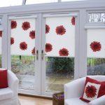 Роликовые шторы с цветами и подушками в тон для комнаты с выходом на улицу