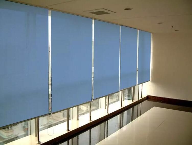 Голубые рулонные шторы на панорамном окне
